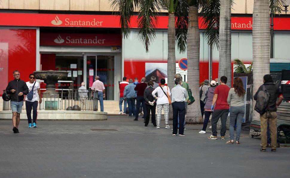 Numerosas personas hacen cola para entrar en una oficina bancaria del Banco Santander durante el estado de alarma. EFE/ Cristóbal García