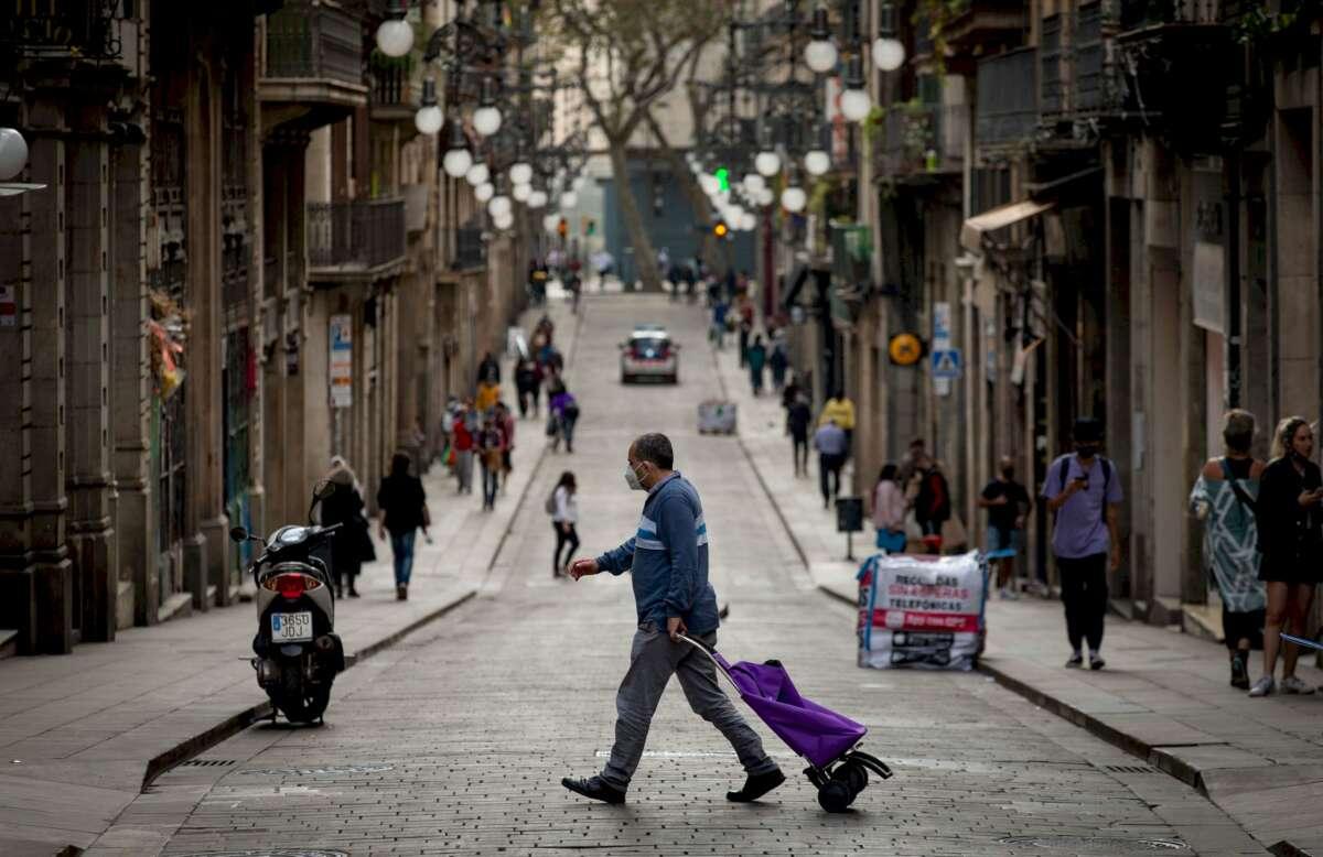 Un vecino de Barcelona se dirige a realizar sus compras por el centro de la ciudad, en plena pandemia de coronavirus | EFE/Enric Fontcuberta/Archivo