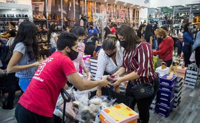 Personas compran en una tienda con ofertas por Black Friday./ EFE