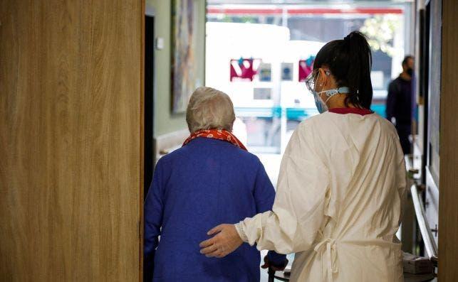Una trabajadora de una residencia de mayores ayuda a una paciente. EFE/David Fernández/Archivo