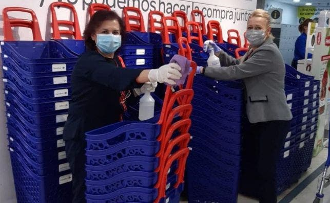 Empleados de Carrefour desinfectan los carros de la compra para evitar contagios por coronavirus.