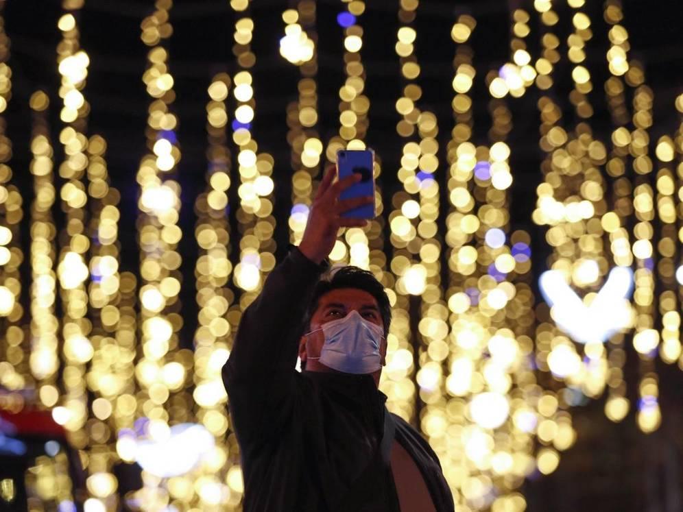 Un transeúnte se fotografía con las luces de Navidad del centro de Barcelona. (EFE)