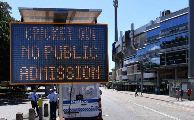 Un cartel advierte a los espectadores de que el One Day International (ODI) entre Australia y Nueva Zelanda se jugará a puerta cerrada en medio de la pandemia del coronavirus, en Sídney, Australia. EFE/EPA/DEAN LEWINS