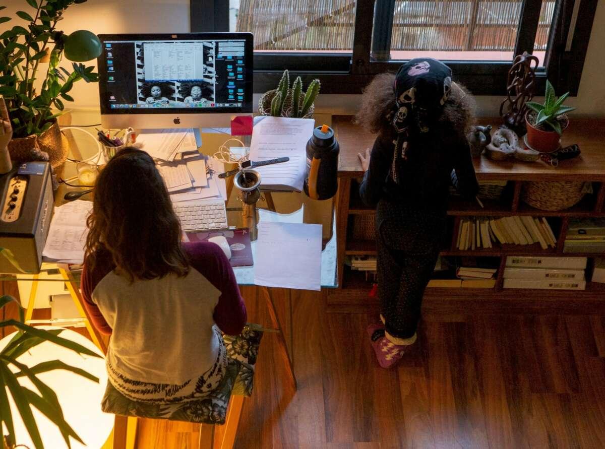 Una mujer realiza teletrabajo en su casa mientras su hija juega a su lado./ EFE