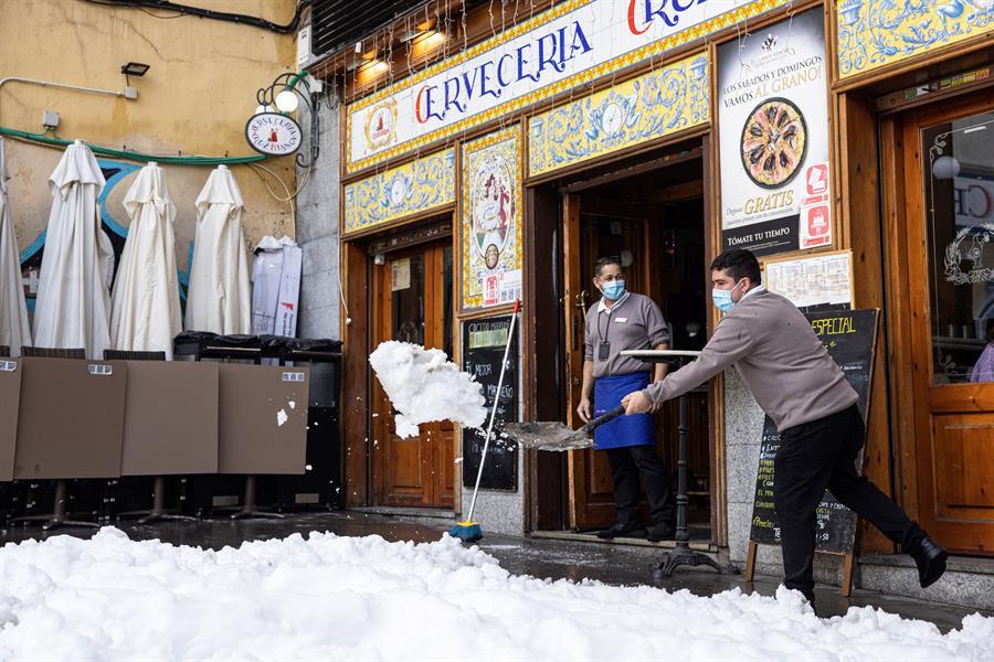Personal de hostelería limpian de nieve las terrazas de los establecimientos en Madrid, este domingo. EFE/Rodrigo Jiménez