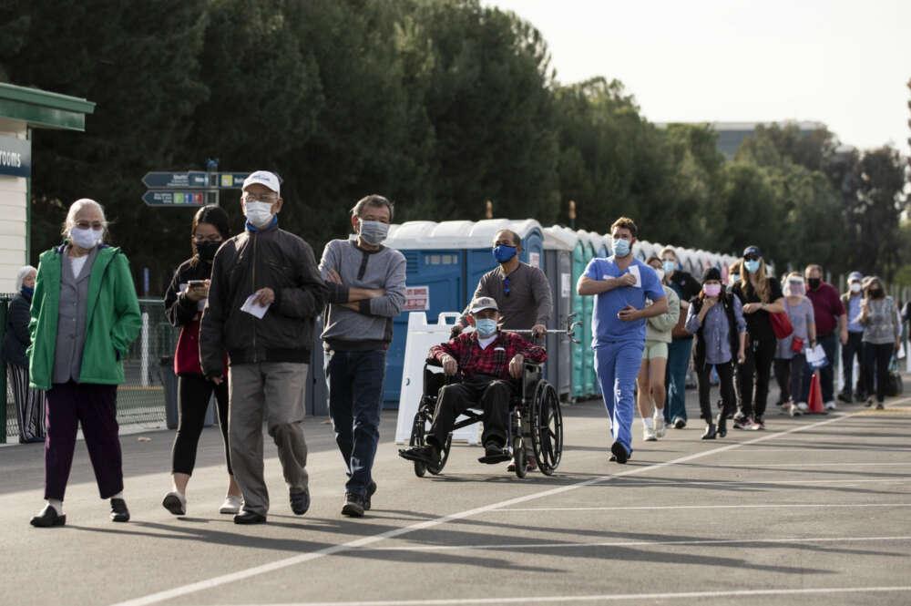 Personas hacen fila para recibir la vacuna contra la covid-19 en Disneyland, de Anaheim, California, este 13 de enero de 2021. EFE/Etienne Laurent