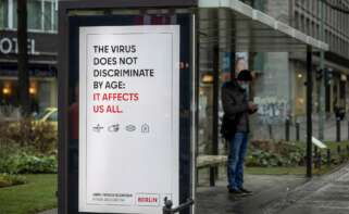 Un cartel advierte del riesgo de contagio de la covid 19 para cualquier edad, en una parada de autobús en Berlin. EFE/EPA/HAYOUNG JEON