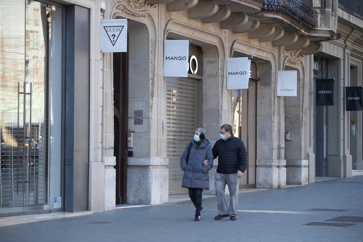 Una pareja pasa por delante de varias tiendas de ropa cerradas este sábado en Barcelona. La tercera ola de la epidemia de COVID sigue aumentando en Cataluña, donde en la última semana se han diagnosticado 24.716 nuevos contagios, 4.527 de ellos ayer, y 408 fallecidos, de los que 64 han sido notificados en las últimas 24 horas. EFE/Marta Pérez