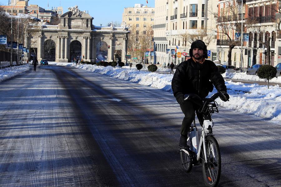 Un hombre circula con una bicicleta del servicio municipal bicimad por calle Alcalá este lunes, tras el paso de la borrasca Filomena. EFE/Fernando Alvarado