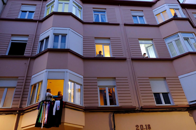 Vecinos de un barrio de Ferrol (Galicia) el 18 de marzo de 2020 viendo el mundo desde sus balcones y ventanas, nada más comenzar el confinamiento total decretado por el Gobierno de Pedro Sánchez para parar la pandemia del coronavirus en España | EFE/KD/Archivo