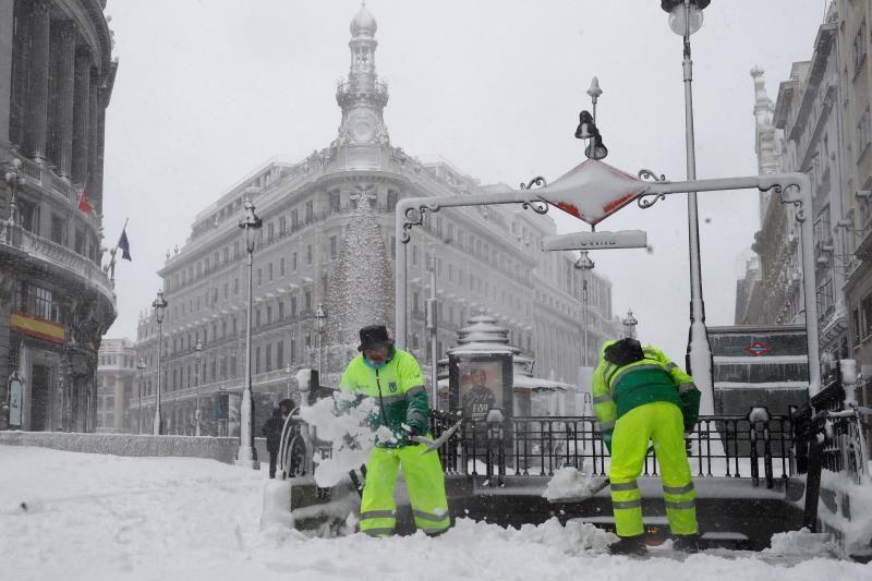 Operarios trabajan para retirar nieve y mejorar la circulación en la Puerta del Sol en Madrid, este sábado. EFE/Ballesteros