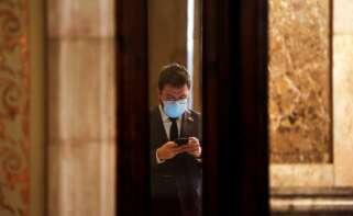 El vicepresidente del Govern con funciones de Presidente, Pere Aragonés, consulta su móvil en los pasillos del Parlament. EFE/Quique García