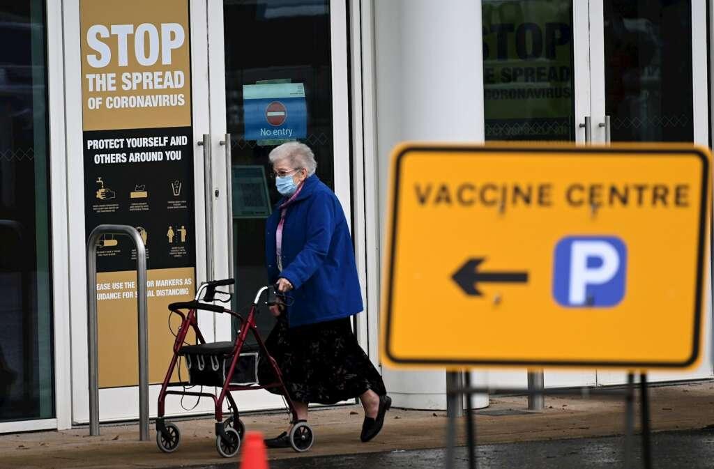 Una mujer sale de un centro de vacunación masiva en Empton, Reino Unido. EFE/ Andy Rain