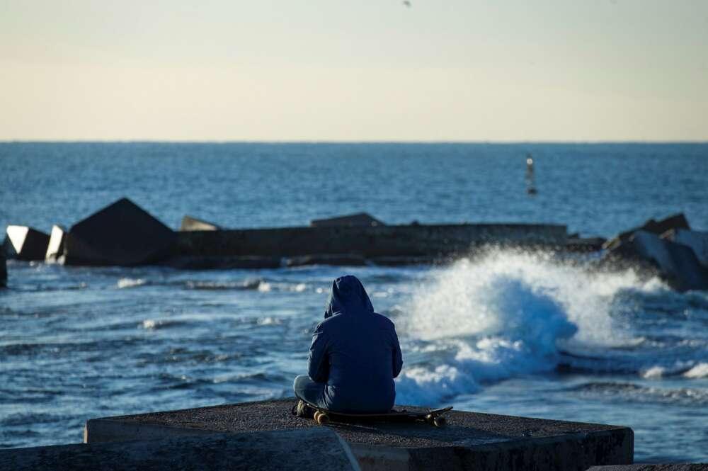 Una persona observa el mar en la playa de Somorrostro este sábado, momento en el que la tercera ola de la epidemia de COVID sigue aumentando en Cataluña./ EFE