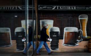 Un hombre pasa junto a un bar cerrado en la localidad guipuzcoana de Andoain. EFE/Javier Etxezarreta