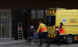 """Dos técnicos de emergencias trasladan a un paciente al nuevo """"hospital satélite"""" del Hospital Universitario de Bellvitge este lunes. EFE/Alejandro García"""