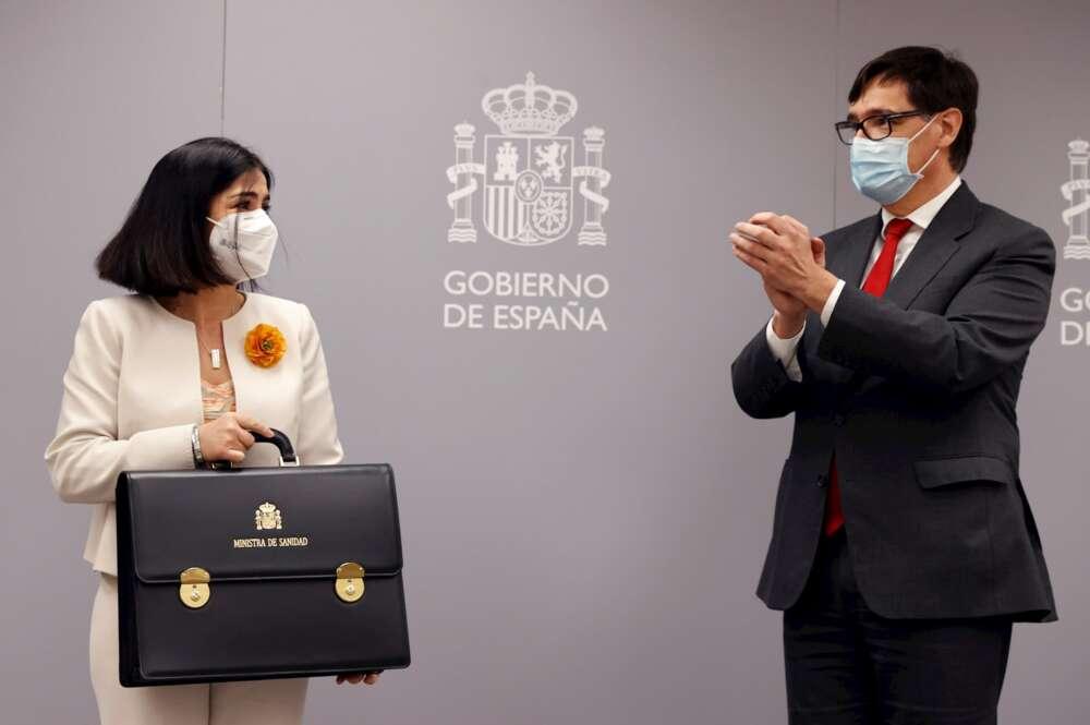 La nueva ministra de Sanidad, Carolina Darias, recibe los aplausos de su predecesor Salvador Illa mientras posa con su nuevo maletín tras la ceremonia de traspaso de la cartera celebrada en el Ministerio de Sanidad, el 27 de enero de 2021 | EFE/CM/Archivo