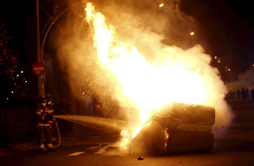Un bombero apaga un contenedor en llamas durante la manifestación de este viernes, en Barcelona. EFE/Quique García