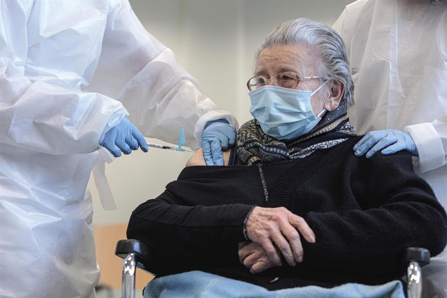 Una anciana recibe una vacuna contra el coronavirus, que ha permitido que los casos sintomáticos y graves bajen radicalmente / EFE
