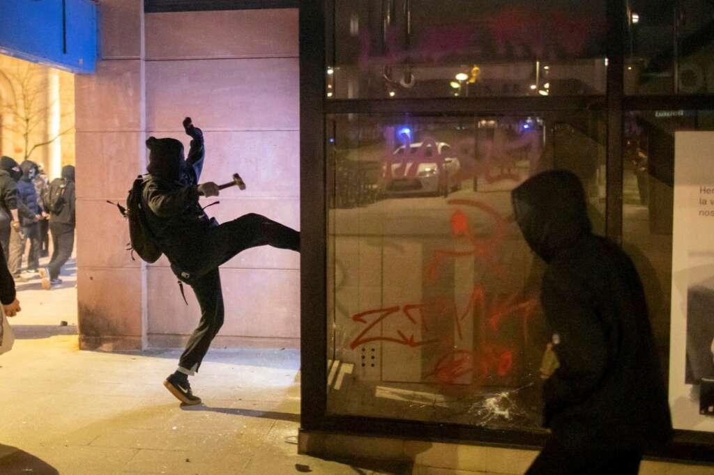 Un joven ataca un comercio durante los disturbios posteriores a la manifestación celebrada este viernes en Girona en protesta por la detención del rapero Pablo Hasél, acusado de delitos de enaltecimiento del terrorismo e injurias a la Corona. EFE/Toni Vilches