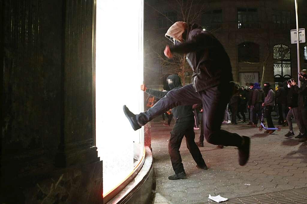 Manifestantes tratan de romper un escaparate de una tienda en el centro de Barcelona, el 20 de febrero de 2021, durante las protestas por el encarcelamiento del rapero Pablo Hasél   EFE/QG/Archivo