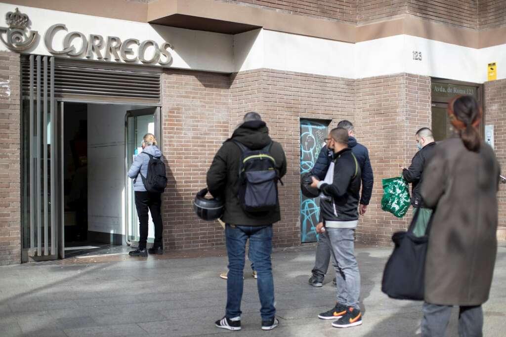 Varias personas hacen cola en una oficina de Correos de Barcelona este viernes, último día para admitir peticiones de voto por correo para el 14F. EFE/ Marta Pérez