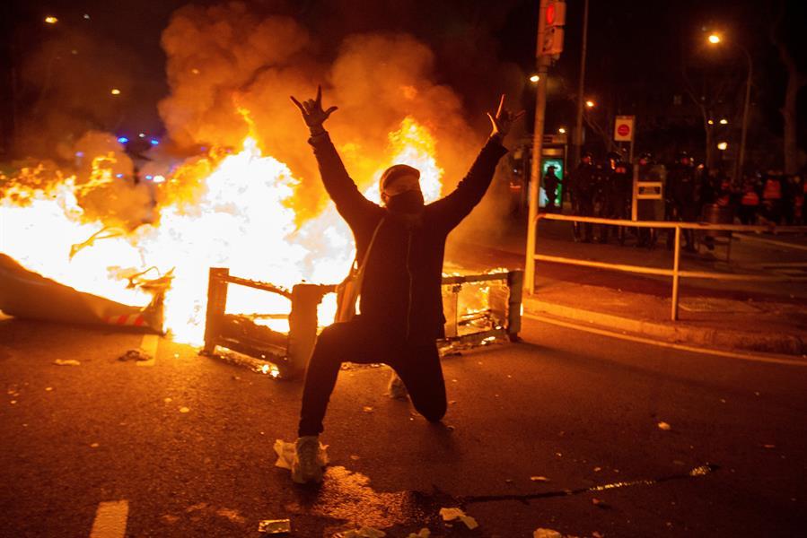 Un manifestante junto a una hoguera en la manifestación de protesta por la detención del rapero Pablo Hasel, que ayer ingresó en prisión, condenado por delitos de enaltecimiento del terrorismo e injurias a la Corona, este miércoles en Barcelona. EFE/Enric Fontcuberta