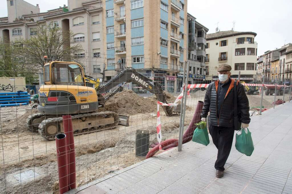 Un vecino pasaba junto a una obra parada en el Coso Bajo de Huesca por las restricciones del primer estado de alarma, en marzo. EFE/ Javier Blasco
