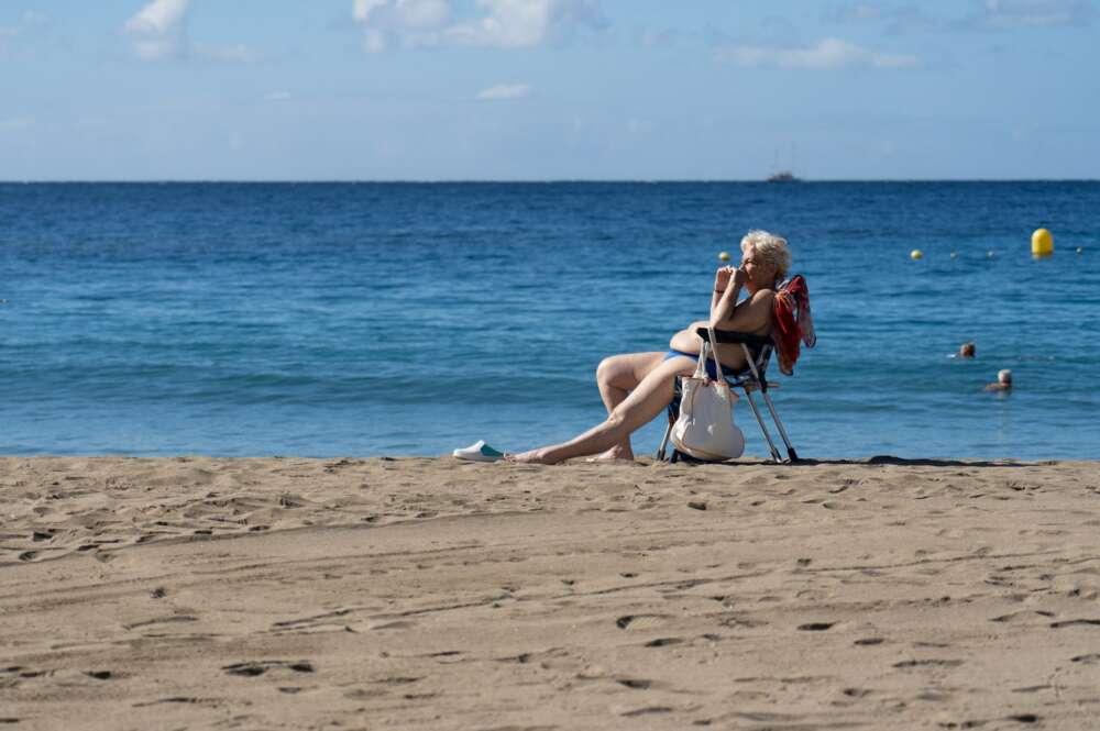 Unos turistas disfrutan de las buenas temperaturas en la playa de Las Vistas en la localidad de Los Cristianos (sur de Tenerife). EFE/Ramón de la Rocha/Archivo