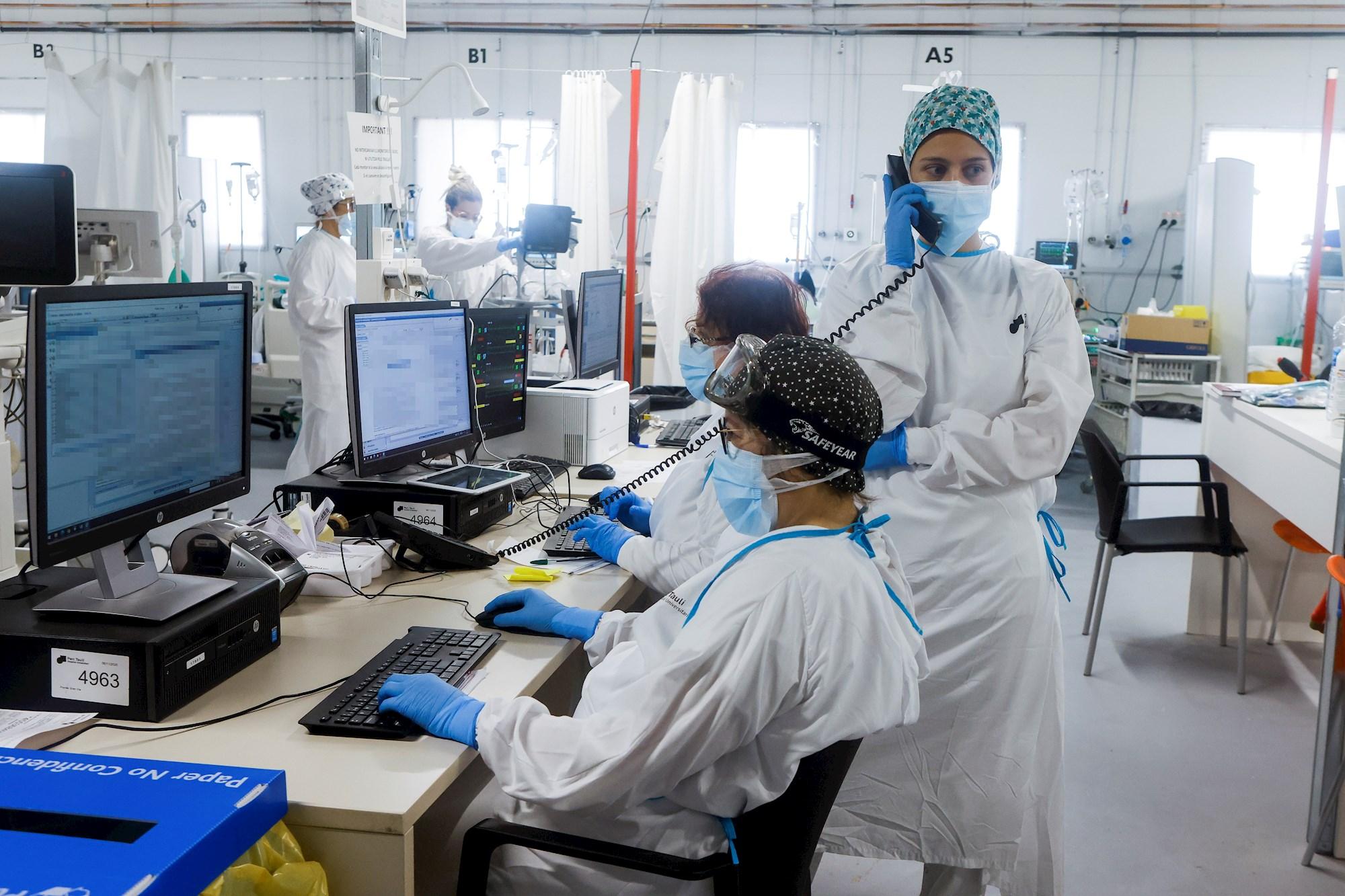 Cataluña registra un nuevo repunte de ingresos por coronavirus. Personal sanitario del Hospital Parc Taulí de Sabadell (Barcelona) en la UCI para enfermos de COVID-19. EFE/Quique Garcia/Archivo