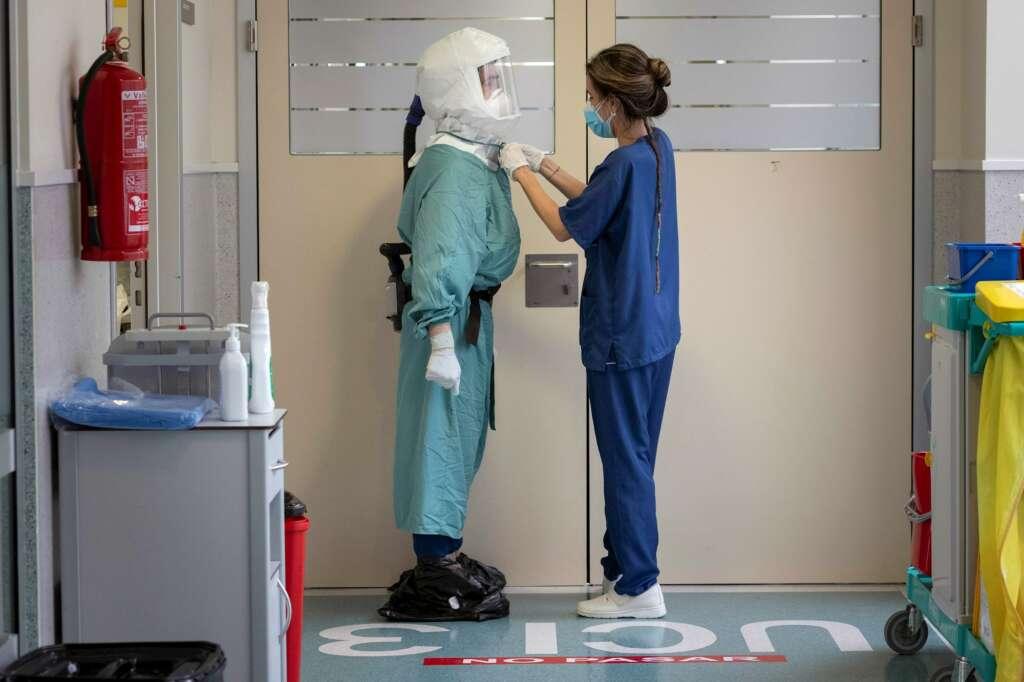 Una enfermera ajusta el Equipo de Protección Personal a un enfermero antes de entrar a un box de la Unidad de Cuidados Intensivos del Hospital Santa Lucia de Cartagena. EFE/Marcial Guillén/Archivo