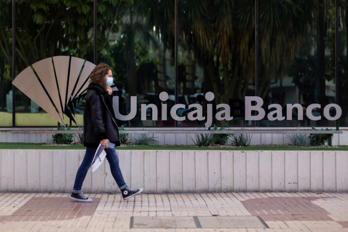 Una mujer pasa ante la sede de Unicaja en Málaga, antes de que se formalice su fusión definitiva con Liberbank que reducirá la competencia en el medio rural. EFE/Carlos Díaz