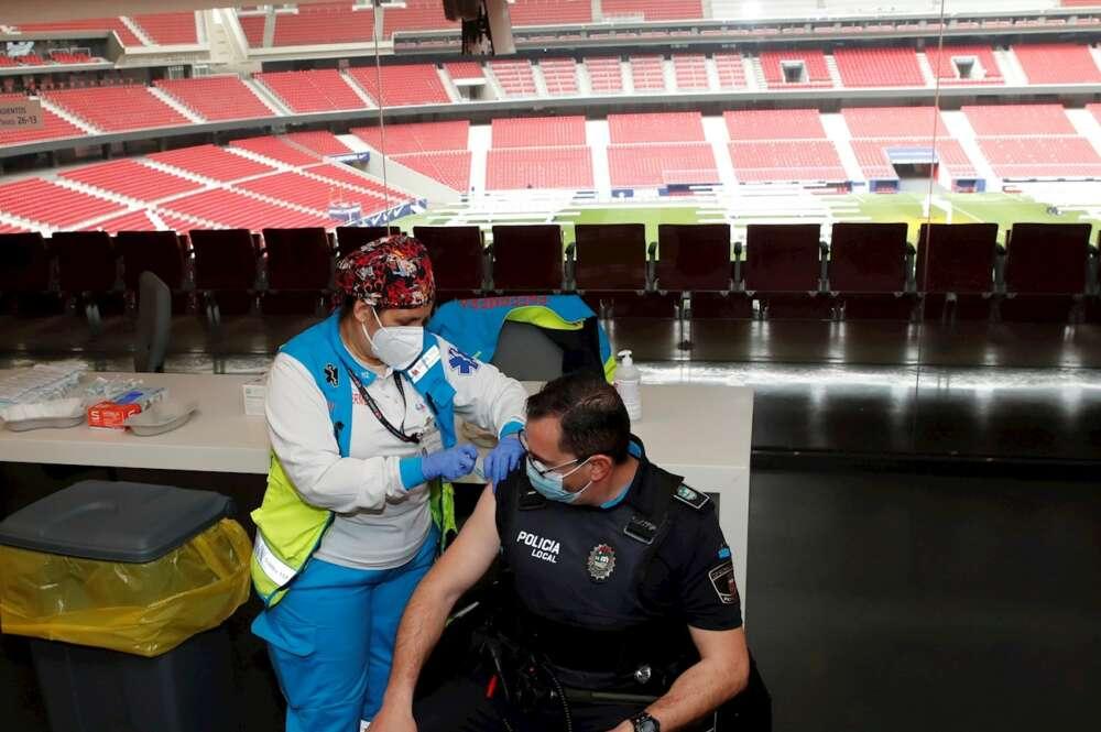 Un policía recibe la primera dosis durante el primer día de vacunación contra la covid-19 en el Wanda Metropolitano. EFE/Juan Carlos Hidalgo