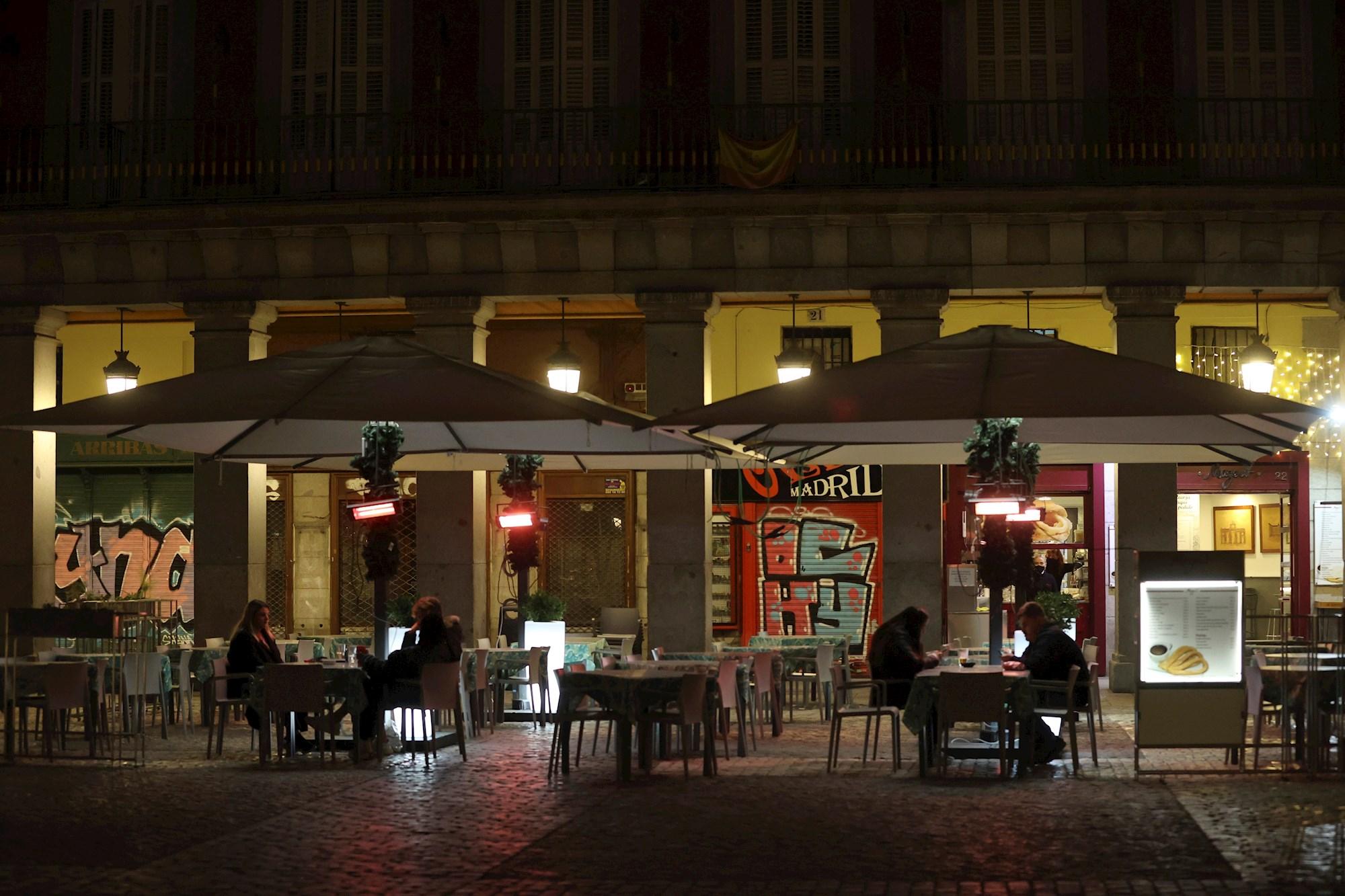 Varias personas toman algo en un bar de Madrid, condicionado por la imposición del toque de queda. EFE/Juanjo Martín