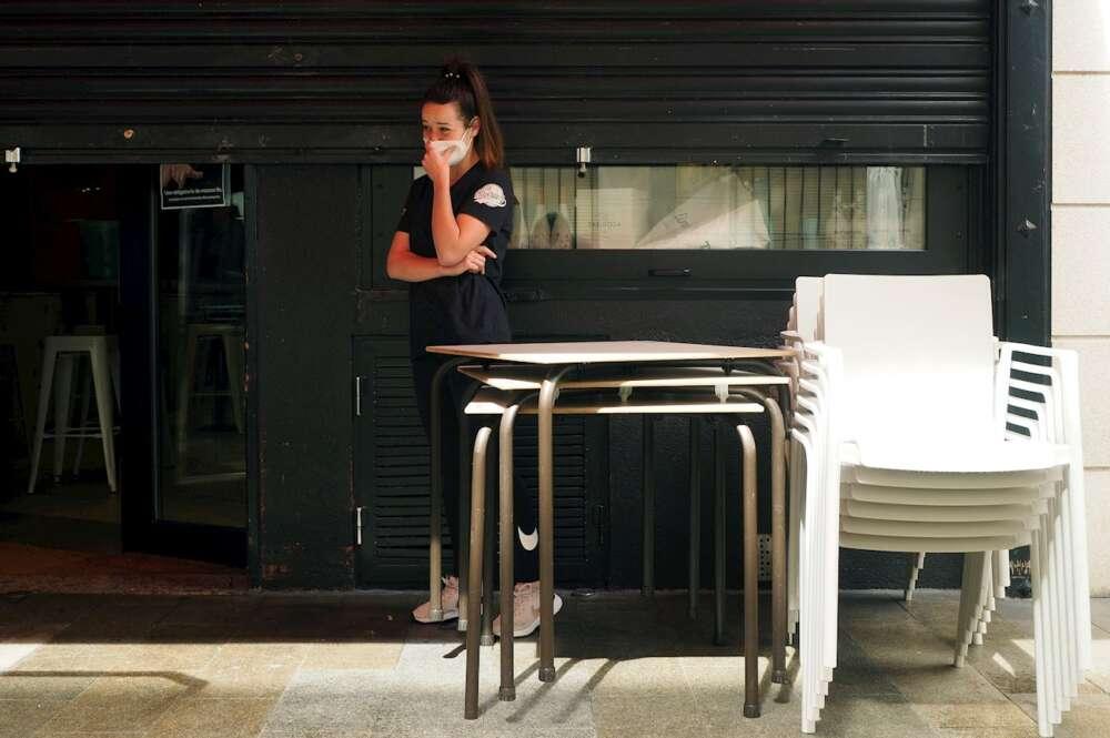 Una trabajadora junto al local en el que trabaja cerrado por coronavirus en el barrio de A Milagrosa en Lugo. EFE/ Eliseo Trigo/Archivo