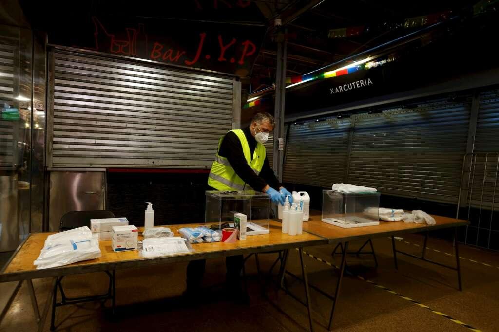 Un operario procede a colocar las mesas, cabinas y urnas del 14-F en el Mercado del Ninot de Barcelona, el 10 de febrero de 2021 | EFE/QG