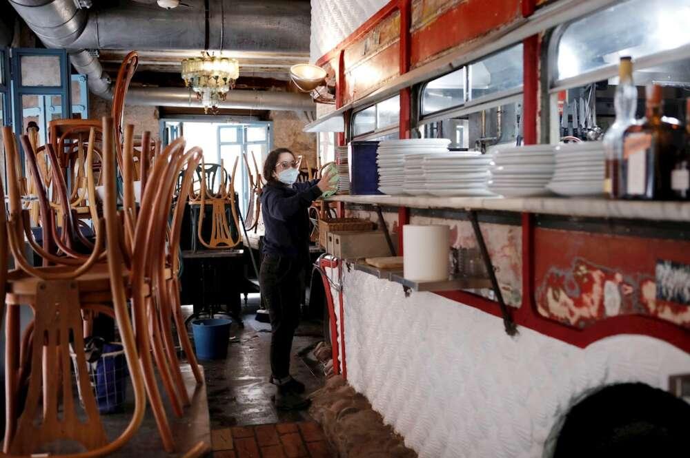 La encargada de un local realiza labores de limpieza y preparación ante la próxima apertura de la hostelería en la Comunidad Valenciana tras el severo plan de restricciones. EFE/ Biel Aliño