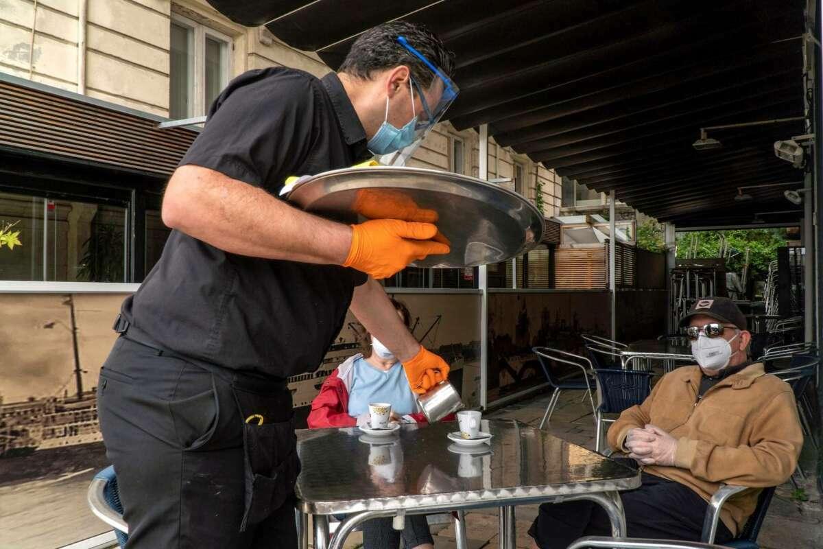Un hombre limpia las mesas de la terraza./ EFE