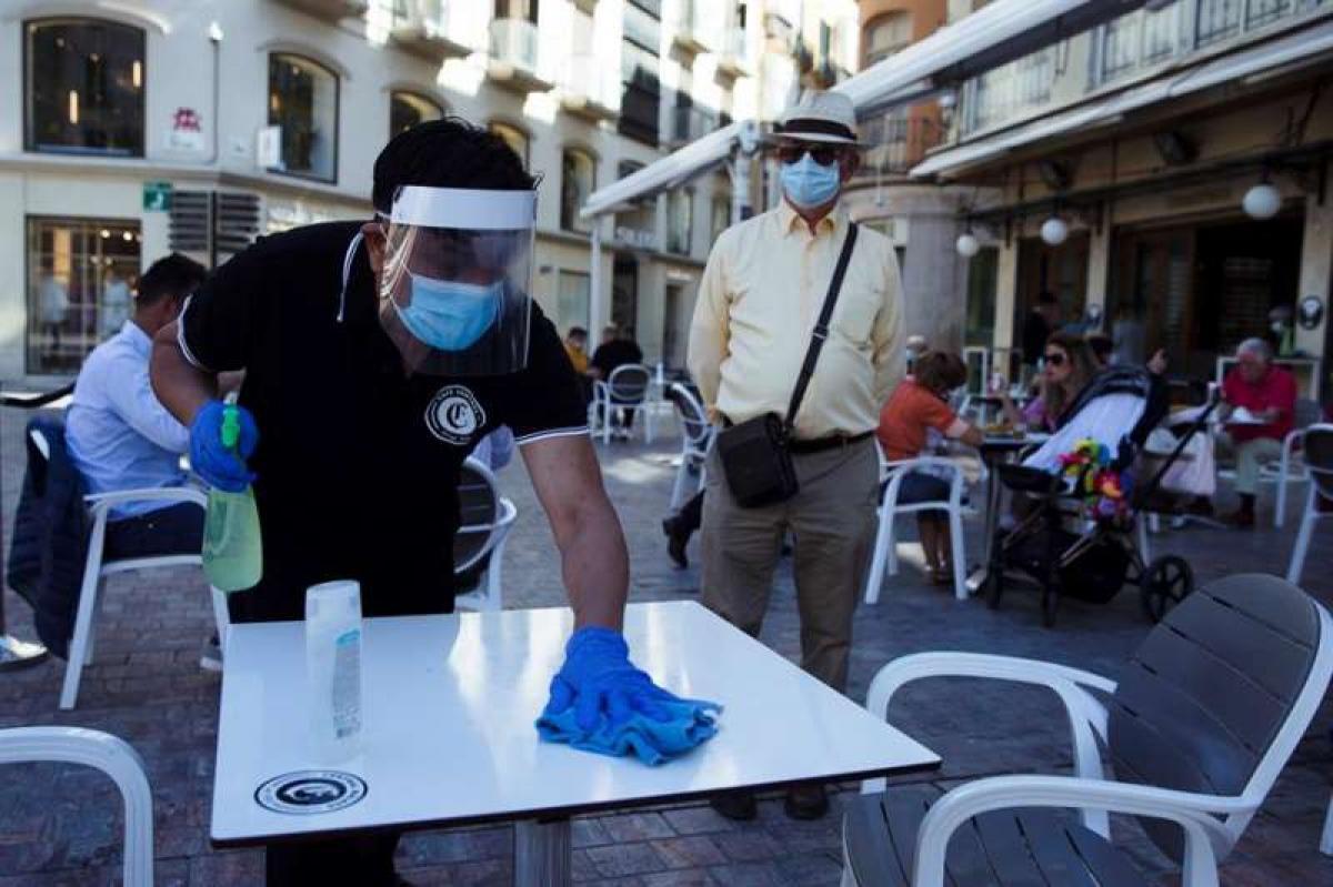 Un camarero limpia la mesa de una terraza antes de que se siente un cliente./ EFE