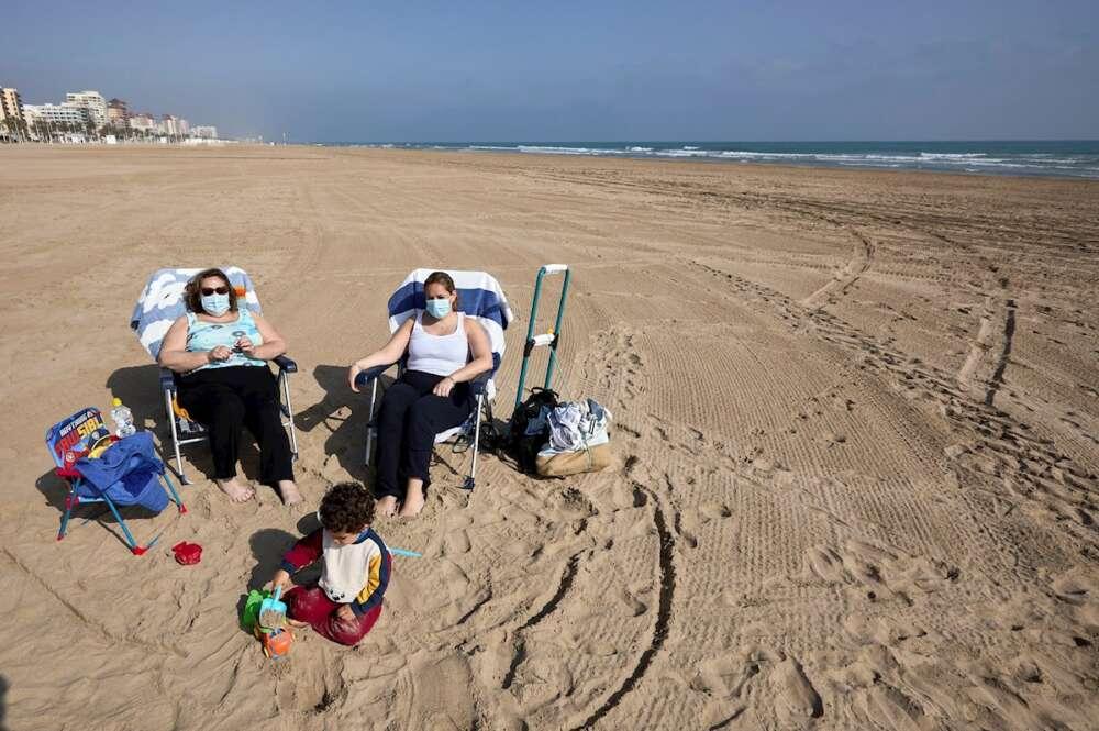 Varias personas toman el sol en la playa de Gandía (Valencia) con la mascarilla, de uso obligatorio incluso cuando se respeta la distancia de seguridad   EFE/NF