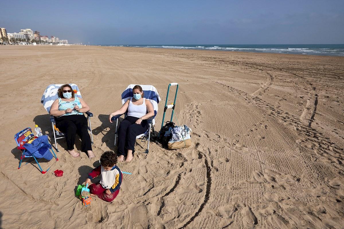 Varias personas toman el sol en la playa de Gandía (Valencia) con la mascarilla, de uso obligatorio incluso cuando se respeta la distancia de seguridad | EFE/NF