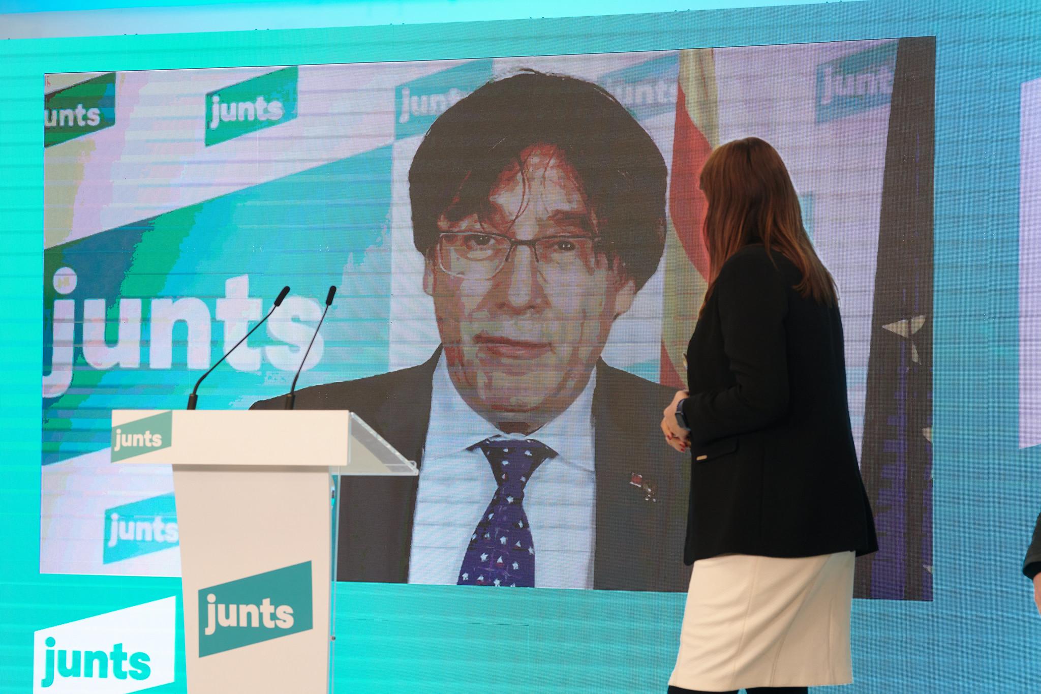 La líder de Junts per Catalunya en el Parlament, Laura Borràs, frente a una pantalla con el prófugo Carles Puigdemont / JxCat