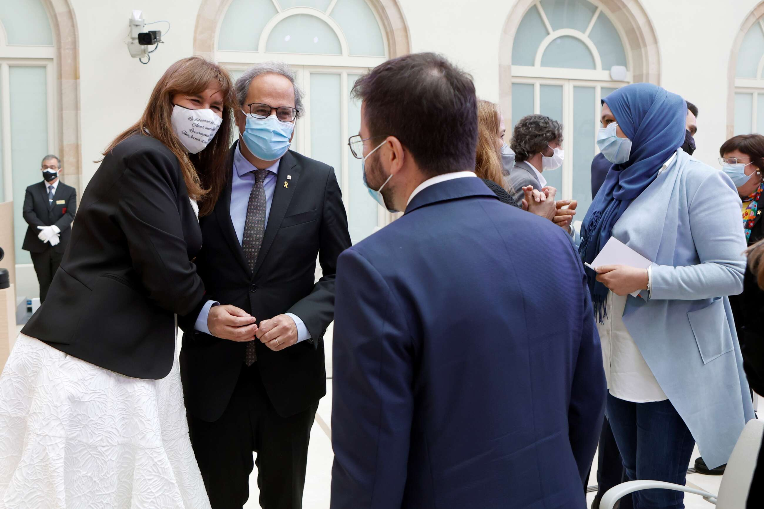 La presidenta del Parlament, Laura Borràs (Junts), abrazada al expresidente Quim Torra, mientras conversa con Pere Aragonès (ERC)