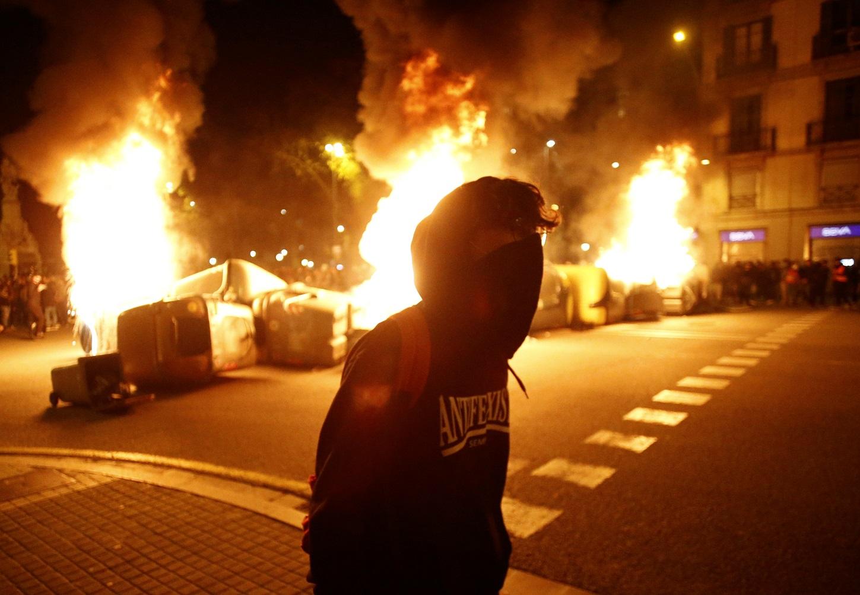 Un manifestante con contenedores ardiendo detrás en la cuarta noche de protestas por la detención del rapero Pablo Hasél, el 19 de febrero de 2021 en Barcelona | EFE/QG/Archivo