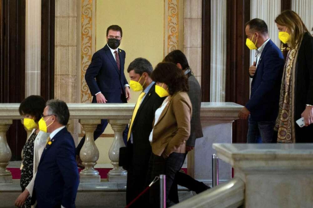 El candidato de ERC, Pere Aragonés, junto a varios diputados de JxCat, en los pasillos del Parlament durante un receso del debate de investidura del nuevo presidente de la Generalitat que se celebra este viernes en el Auditori del Parlament de Catalunya. EFE/Enric Fontcuberta