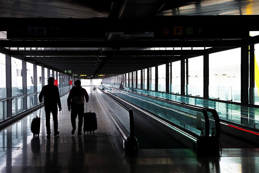 Dos pasajeros cruzan una de las terminales del Aeropuerto Adolfo Suárez Madrid-Barajas. EFE/Emilio Naranjo/Archivo