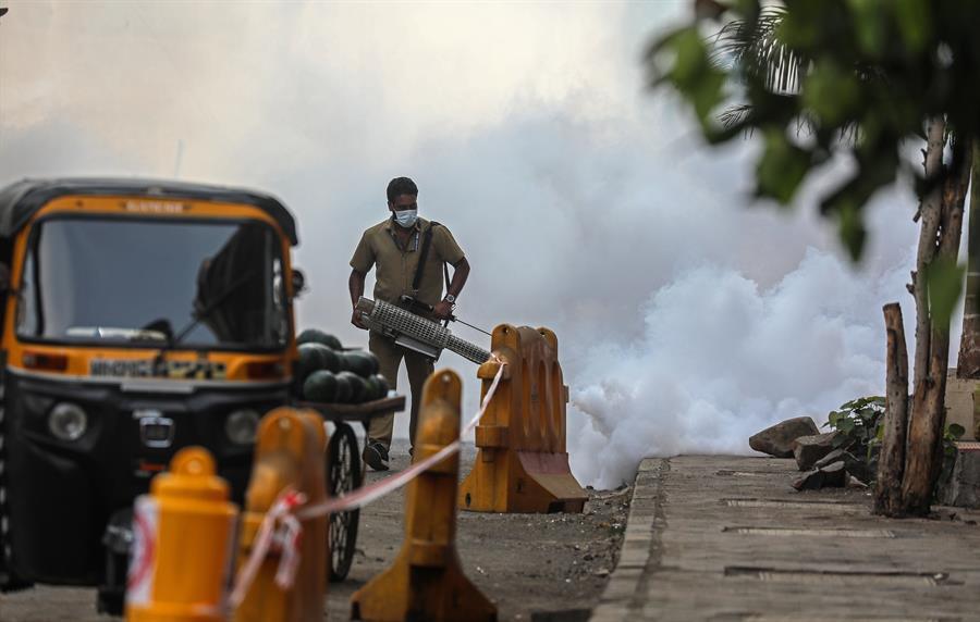 Un trabajador municipal que lleva una mascarilla utiliza una máquina de fumigación en aerosol cerca de un centro de vacunación en Mumbai, India, el 30 de abril de 2021. India ha registrado recientemente un aumento masivo de casos y muertes por COVID-19, el aumento más alto en un día desde la comienzo de la pandemia. EFE / EPA / DIVYAKANT SOLANKI