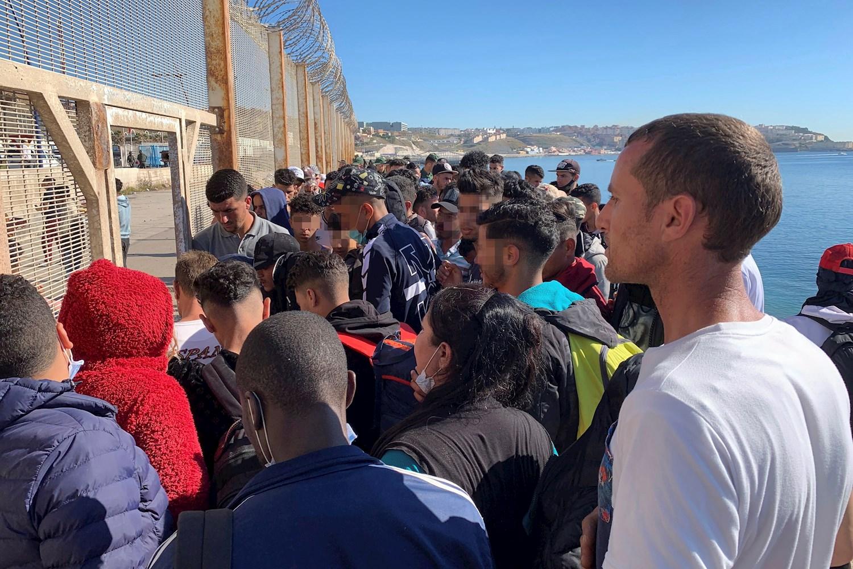 Un grupo de personas intenta cruzar la valla fronteriza que separa Fnideq (Castillejos, Marruecos) de la ciudad española de Ceuta, ubicada en el norte de África, 19 de mayo de 2021./ EFE