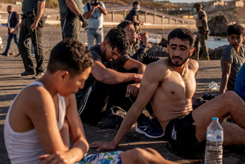 Varios migrantes descansan en la playa ceutí de El Tarajal tras alcanzar la costa española este miércoles. Tercer día de tensión en la frontera de Ceuta con Marruecos, después de la entrada ilegal en la ciudad autónoma de más de 8.000 personas y con el Ejército y las fuerzas de seguridad desplegados en la zona. EFE/Brais Lorenzo
