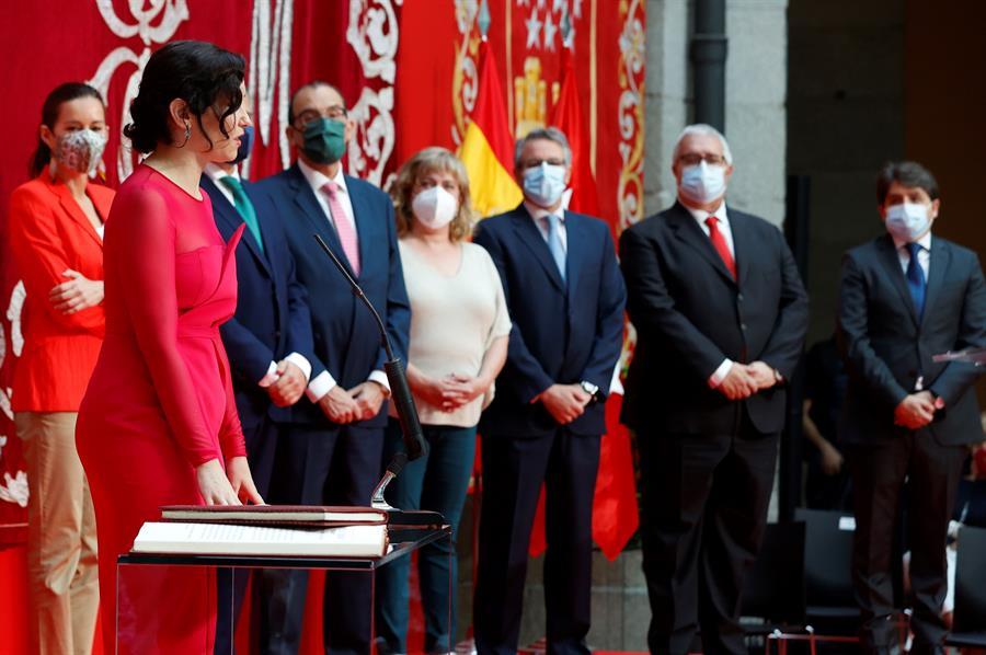 La presidenta de la Comunidad de Madrid, Isabel Díaz Ayuso (i) jura su cargo durante su investidura celebrada en la Real Casa de Correos este sábado. EFE/J.J. Guillén